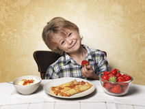 Boy, breakfast, eating strawberry pancakes Royalty Free Stock Photos