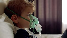 Boy breathes through the transparent mask of the inhaler. The boy himself makes. Inhalation mask on the face of the pat stock footage
