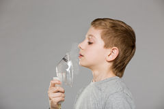 Boy breathing from inhalator mask releasing smoke Stock Photography