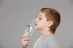 Boy breathing from inhalator mask releasing smoke Stock Photography