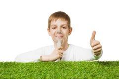 Boy breathing through inhalator mask thumb up Stock Photography