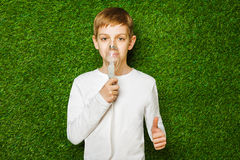 Boy breathing through inhalator mask thumb up Stock Image