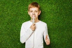 Boy breathing through inhalator mask thumb up Stock Image