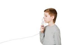 Boy breathing through inhalator mask on white background Stock Photos
