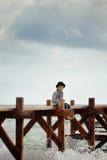 Boy on the bridge at the sea Stock Image