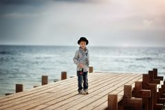 Boy on the bridge at the sea Stock Photography