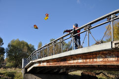Boy on bridge thinks throws maple leaf in water Stock Photo