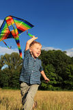 Boy with bright kite over the head Royalty Free Stock Photography