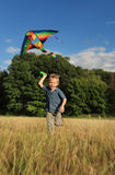 Boy with bright kite over the head Stock Images