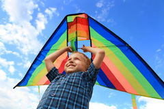 Boy with bright kite over the head Stock Photography