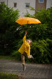 Boy in bright yellow raincoat flies over the earth with an umbrella in a hand. Stock Image
