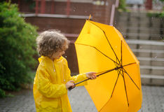The boy in a bright yellow raincoat opens an umbrella during arain. Stock Photo