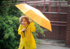 The boy in a bright yellow raincoat to stand under pouring rain. Royalty Free Stock Photos