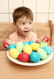Boy with brightly colored eggs. Small boy sitting at a kitchen table before a bowl of brightly colored eggs whilst holding two red eggs in his hands Royalty Free Stock Photos