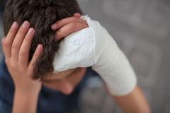 Boy with broken arm touching head royalty free stock images