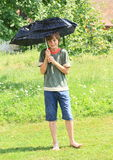 Boy with broken black umbrella Stock Photos