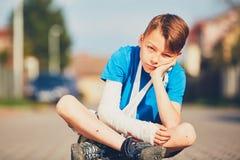 Boy with broken hand. Mischievous boy with broken hand injured after accident during summer sports Stock Photos