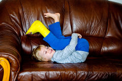 Boy with broken leg in cast lying on couch. Royalty Free Stock Images