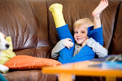 Boy with broken leg in cast sitting on couch. Stock Images