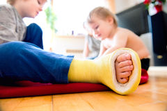 Boy with broken leg with his brother playing. Royalty Free Stock Photo