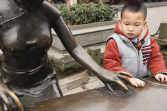 Boy bronze statue. One Chinese boy stand by bronze statue playing Chinese Zither Royalty Free Stock Photo