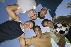 Boy (13-15) with brothers and father in huddle view from below. Stock Image