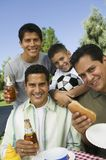Boy (13-15) with brothers and father at outdoor picnic portrait Royalty Free Stock Image