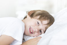 Boy with brown eyes lying on a white pillow Royalty Free Stock Photo