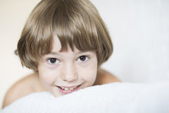 Boy with brown eyes lying on a white pillow Stock Photo