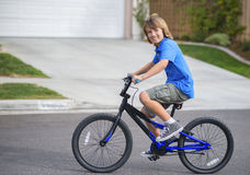 Happy Boy Riding Bike. A boy with brown hair and eyes, wearing a blue shirt, smiles as he rides his bike on a suburban neighborhood street Royalty Free Stock Photo