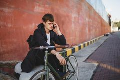 Boy with brown hair sitting while leaning on bicycle and talking on his cellphone. Young man in down jacket and black. Portrait of boy with brown hair sitting Royalty Free Stock Photo