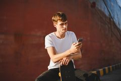 Boy with brown hair sitting with skateboard in hand and thoughtfully looking in cellphone. Young man in white t-shirt. Portrait of boy with brown hair sitting Stock Photo