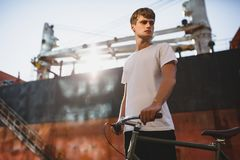 Boy with brown hair standing with bicycle and thoughtfully looking aside. portrait of young man in white t-shirt. Photo of boy with brown hair standing with Stock Image