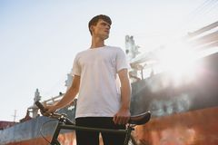 Boy with brown hair standing with bicycle and thoughtfully looking aside. Young man in white t-shirt standing and posing. Portrait of boy with brown hair Stock Images