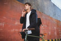 Boy with brown hair standing with classic bicycle and dreamily looking aside while talking on his cellphone. Young man. Portrait of boy with brown hair standing Royalty Free Stock Photography