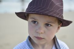 Boy with a brown hat looking very serious. Boy, with a brown hat and white shirt on, looking very serious at the beach Stock Photos