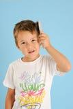 Boy brushing his hair Royalty Free Stock Image