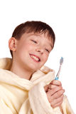 A boy brushing his teeth after bath. A boy wearing a yellow bathrobe, brushing his teeth isolated on white background Royalty Free Stock Photography