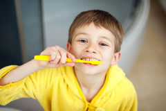 Boy brushing his teeth in bathtub, smiling. healthy lifestyle concept stock images