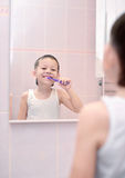 Boy brushing his teeth in front of mirror Stock Photos