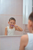 Boy brushing his teeth in front of mirror Stock Images