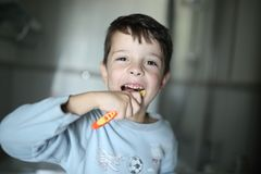 The boy is brushing his teeth with happy expression on the face stock image