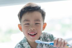 A boy is brushing his teeth in the morning on the bed stock photos