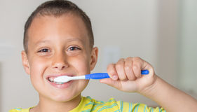 Boy brushing his teeth and smiling. Stock Image