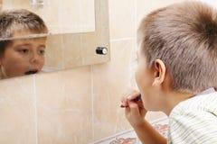 Boy brushing teeth Stock Images