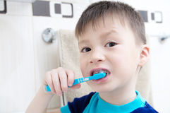 Boy brushing teeth, child dental care, oral hygiene concept, boy portrait in bathroom with tooth brush. Healthy lifestyle Stock Photos