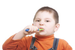 Boy brushing teeth with effort Royalty Free Stock Photos