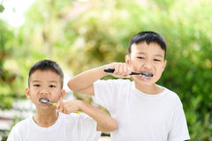 Boy brushing teeth in the garden royalty free stock photos