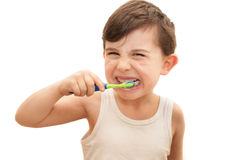 Boy brushing teeth isolated. Young boy brushing his teeth on an isolated white background. The boy is six hears old and has four new adult teeth that have stock images