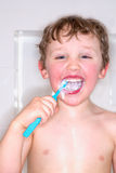Boy brushing teeth and laughing, messy toothpaste. Royalty Free Stock Image